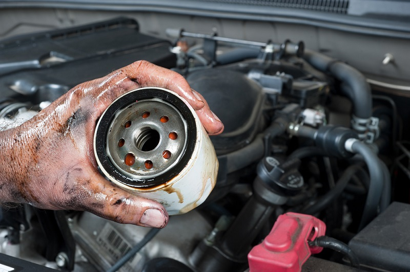 An auto mechanic shows an old, dirty oil filter just removed from a car during general maintenance